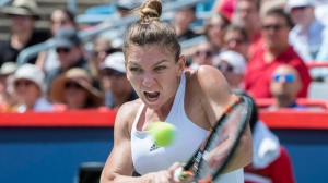 Simona Halep, of Romania, returns to Angelique Kerber, of Germany, during women's semifinal Rogers Cup tennis action, in Montreal on Saturday, July 30, 2016. Halep won 6-0, 3-6, 6-2 to move on to the final, which takes place Sunday. THE CANADIAN PRESS/Paul Chiasson