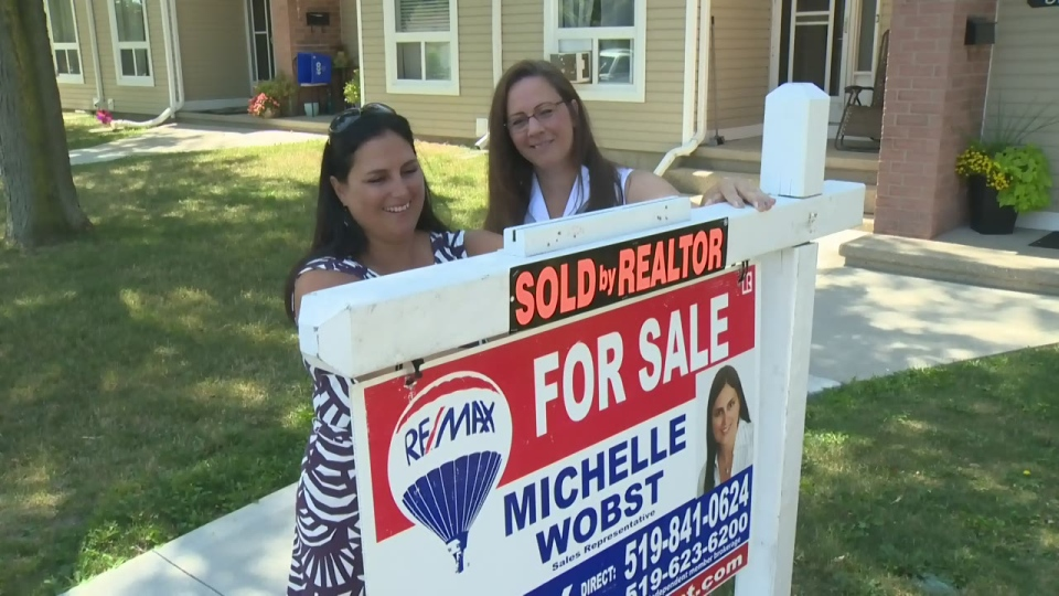 Real estate agent Michelle Wobst and homeowner Susan Lankowski stand behind a 'sold' sign at Lankowski's home in Kitchener on Thursday, Aug. 4, 2016.