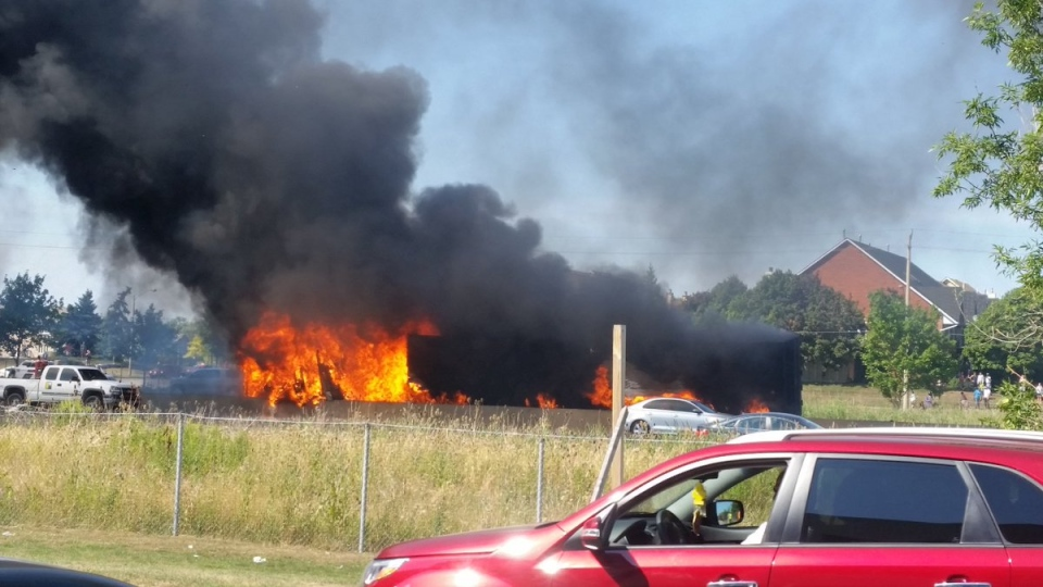 A fire burns at the site of a tractor trailer crash on the Queen Elizabeth Way on Thursday. (Twitter.com/@anTonucci)