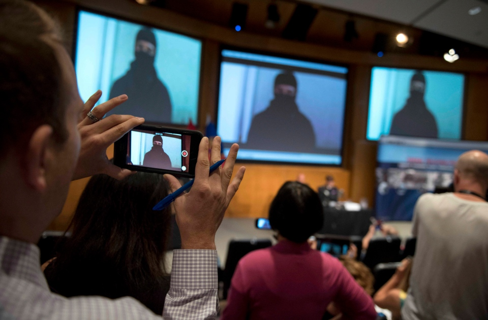 Reporters record video footage showing Aaron Driver during a press conference for what the RCMP are calling a terrorism incident, in Strathroy, Ont., on Thursday, Aug. 11, 2016 in Ottawa. (The Canadian Press/Justin Tang)