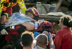 An injured woman is carried by rescuers in Amatrice, central Italy, where a 6.1 earthquake struck just after 3:30 a.m., Italy, 24 August 2016. The quake was felt across a broad section of central Italy, including the capital Rome where people in homes in the historic center felt a long swaying followed by aftershocks. (Massimo Percossi/ANSA via AP)