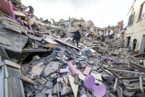 People walk on rubble following an earthquake in Amatrice Italy, Wednesday, Aug. 24, 2016. The magnitude 6 quake struck at 3:36 a.m. (0136 GMT) and was felt across a broad swath of central Italy, including Rome where residents of the capital felt a long swaying followed by aftershocks. (Massimo Percossi/ANSA via AP)