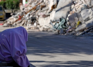 A man sits with a blanket over his head in front of collapsed buildings, in Amatrice, central Italy, Friday, Aug. 26, 2016. Strong aftershocks rattled residents and rescue crews alike Friday as hopes began to dim that firefighters would find any more survivors from Wednesday's earthquake. (AP Photo/Andrew Medichini)