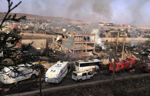 Smoke still rises from the scene after Kurdish militants attacked a police checkpoint in Cizre, southeast Turkey, Friday, Aug. 26, 2016, with an explosives-laden truck, killing several police officers and wounding dozens more, according to reports from the state-run Anadolu news agency. The attack struck the checkpoint some 50 meters (yards) from a main police station near the town of Cizre, in the mainly-Kurdish Sirnak province that borders Syria. (DHA via AP)