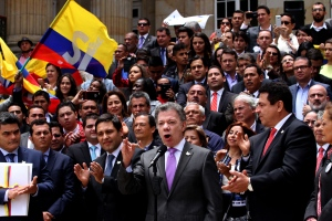 Colombia's President Juan Manuel Santos, front, second from right, speaks after delivering to Congress the peace deal with rebels of the Revolutionary Armed Forces of Colombia, FARC, in Bogota, Colombia, on Thursday, Aug. 25, 2016. (AP Photo/Felipe Caicedo)