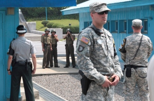 In this July 27, 2014 file photo, North Korean army soldiers watch the south side while a South Korean and United States Army soldiers stand guard at the border villages of Panmunjom in Paju, South Korea. North Korea has threatened on Saturday, Aug. 27, 2016, to aim fire at the lighting equipment used by American and South Korean troops at a truce village inside the Demilitarized Zone that divides the two Korea. (AP Photo/Ahn Young-joon, File)