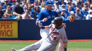 Minnesota Twins' Trevor Plouffe slides safely into third base in front of Toronto Blue Jays' Josh Donaldson during fourth inning Major League baseball action against the Minnesota Twins in Toronto on Saturday, August 27, 2016. THE CANADIAN PRESS/Chris Young