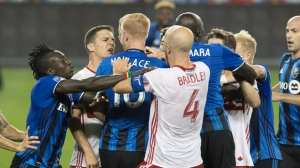 Toronto FC's Will Johnson, second from left, and Montreal Impact's Calum Mallace exchange words at midfield as team mates try to pull them apart during first half MLS soccer action in Toronto on Saturday, August 27, 2016. THE CANADIAN PRESS/Fred Thornhill