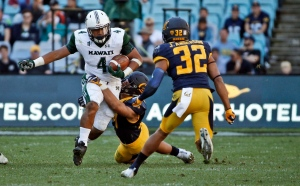 Hawaii Warriors running back Steven Lakalaka, left, is tackled by California Golden Bears linebacker Jordan Kunaszyk during the opening game of the U.S. College football season in Sydney, Australia, Saturday, Aug. 27, 2016. The last American football of any kind played in Sydney was an NFL preseason game at the Olympic stadium that attracted 73,000 spectators in 1999. (AP Photo/Rob Griffith)