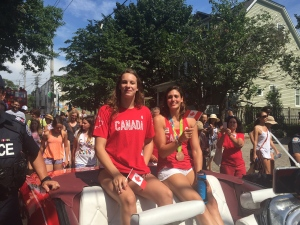 Olympic medalists Penny Oleksiak (left) and Michelle Williams (right) make their way along the route of a parade celebrating Canada's Olympians on Sunday. (Arda Zakarian)