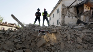 Firefighters operate a drone to survey damaged constructions in the village of Cossito, central Italy, Saturday, Aug. 27, 2016.  Italians bid farewell Saturday to victims of the devastating earthquake that struck a mountainous region of central Italy this week. (AP Photo/Andrew Medichini)