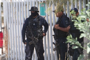 In this May 22, 2015, file photo, Mexican state police stand guard near the entrance of Rancho del Sol, where a shootout with the authorities and suspected criminals happened near Vista Hermosa, Mexico. (AP Photo/Refugio Ruiz)