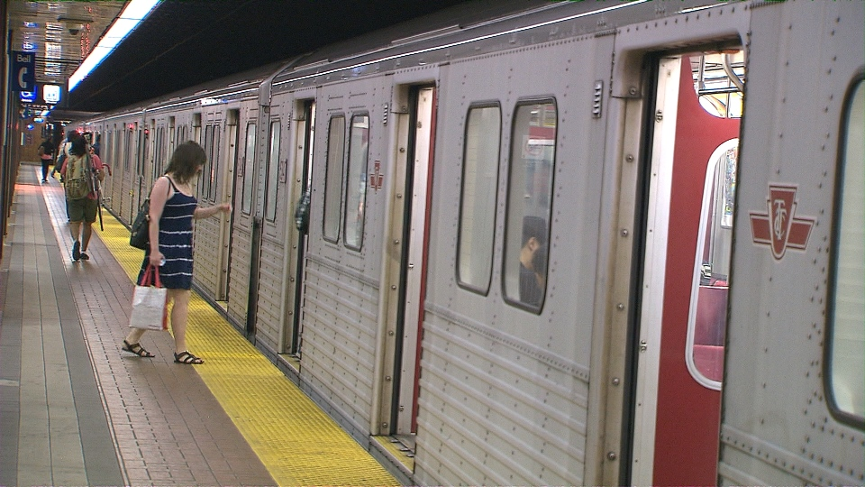 A woman boards a Line 2 subway car on a hot day.