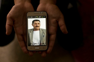 In this Wednesday, May 18, 2016 photo, a relative shows a phone picture of Murat Mahmoud during an interview with the Associated Press at Kankhe Camp for the internally displaced in Dahuk, northern Iraq. Murat was killed on Aug. 3, 2014 by Islamic State militants in a massacre of Yazidis and his body is among 40 believed in a mass grave at a farm on Sinjar Mountain. (AP Photo/Maya Alleruzzo)