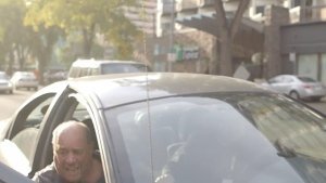 In this still image made from a video posted to Facebook by actor and former high-jump champion Jesse Lipscombe on Wednesday, a man who was caught on camera yelling a racial epithet curses as he closes the door to a grey, four-door sedan before driving off. Lipscombe, who is black, was shooting a public service announcement in Edmonton's downtown about how great the city is, when the man in the vehicle started shouting slurs at him. THE CANADIAN PRESS/HO-Jesse Lipscombe, Facebook