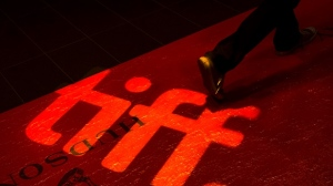A man walks on a red carpet displaying a sign for the Toronto International Film Festival at the TIFF Bell Lightbox in Toronto on Wednesday, Sept. 3, 2014. (Darren Calabrese / THE CANADIAN PRESS)