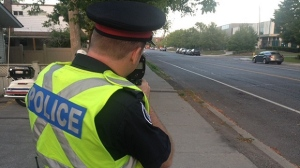 A Toronto police is shown using a radar gun in this file photo. (Cam Woolley/CP24)