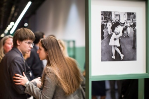 "People speak next to a famous photograph taken by Alfred Eisenstaedt of a sailor kissing a nurse in New York's Times Square on V-J Day, right, as they visit the exhibition of German-American ""Life"" magazine photographer Alfred Eisenstaedt at Moscow's Jewish Museum and Tolerance Center in Moscow, Russia, Tuesday, April 14, 2015. (AP Photo/Alexander Zemlianichenko)"