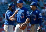 Toronto Blue Jays relief pitcher Danny Barnes, center, gets a pat on the shoulder from catcher Dioner Navarro after he is taken out of a baseball game in the eighth inning against the Los Angeles Angels in Anaheim, Calif., Sunday, Sept. 18, 2016. (AP Photo/Christine Cotter)