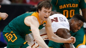 Baylor guard Brady Heslip, left, and Iowa State forward Melvin Ejim (3) chase a loose ball during the first half of an NCAA college basketball game in the final of the Big 12 Conference men's tournament in Kansas City, Mo., Saturday, March 15, 2014. The Toronto Raptors have signed free-agent guard Brady Heslip. THE CANADIAN PRESS/AP, Orlin Wagner