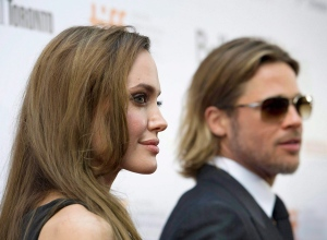 "Brad Pitt and his wife Angelina Jolie pose for a photograph on the red carpet before the screening of this new movie ""Moneyball"" at the Toronto International Film Festival in Toronto on Friday, Sept. 9, 2011. (The Canadian Press/Nathan Denette)"