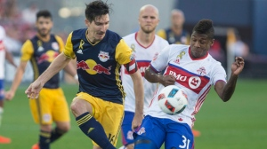 New York Red Bulls' Sacha Kljestan, right, vies for the ball with Toronto FC's Armando Cooper during second half MLS action, in Toronto on Sunday, September 18, 2016. THE CANADIAN PRESS/Chris Young