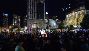Protesters stand in unity in Romare Bearden Park as they prepare to march throughout the city of Charlotte, N.C., Friday, Sept. 23, 2016. Dozens of demonstrators are out in Charlotte for a fourth night of protests after the shooting of a black man by a police officer. People gathered Friday night at a park and then marched through Charlotte's business district with signs. (Jeff Siner/The Charlotte Observer via AP)