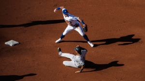 Toronto Blue Jays' Josh Donaldson turns a double play over New York Yankees Aaron Hicks, right during second inning AL baseball action in Toronto, Saturday September 24, 2016. THE CANADIAN PRESS/Mark Blinch