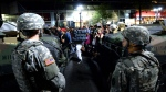 National Guard members watch as protesters march down Tyron Street in Charlotte, N.C. Saturday, Sept. 24, 2016. Protesters came together for the fifth night to protest Tuesday's fatal police shooting of Keith Lamont Scott. (Jeff Siner/The Charlotte Observer via AP)