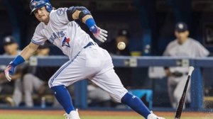Toronto Blue Jays' Josh Donaldson runs out a foul ball against the New York Yankees during the first inning of MLB baseball action in Toronto, Friday September 23, 2016. Donaldson, the reigning AL MVP, turned heads Friday when he took the field combing the old and new knee-high blue socks and gleaming white spikes. The third baseman looked like he was wearing searchlights on his feet. THE CANADIAN PRESS/Mark Blinch