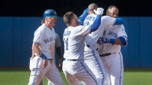 Toronto Blue Jays Edwin Encarnacion (right) is mobbed by teammates (left to right) Josh Donaldson, Kevin Pillar and Ezequiel Carrera after he drove in the winning run in the ninth inning of their American League MLB baseball game against the New York Yankees in Toronto, Sunday, September 25, 2016. THE CANADIAN PRESS/Fred Thornhil