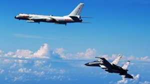 In this Sunday, Sept. 25, 2016, photo released by Xinhua News Agency, Chinese People's Liberation Army Air Force Su-30 fighter, right, flies along with a H-6K bomber as they take part in a drill near the East China Sea. Japan's top government spokesman has warned China against expanding its military activity in the skies over disputed East China Sea islands after eight Chinese warplanes flew near the area on Sunday. (Shao Jing/Xinhua via AP)