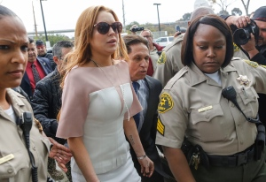 In this file photo dated Monday, March 18, 2013, actress Lindsay Lohan arrives at the Los Angeles Superior court, charged with three misdemeanor counts stemming from a car crash on Pacific Coast Highway. (AP Photo/Damian Dovarganes)
