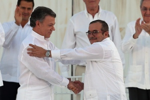Colombia's President Juan Manuel Santos, left, and the top commander of the Revolutionary Armed Forces of Colombia (FARC) Rodrigo Londono, known by the alias Timochenko, shake hands after signing a peace agreement between Colombia's government and the FARC to end over 50 years of conflict in Cartagena, Colombia, Monday, Sept. 26, 2016. (AP Photo/Fernando Vergara)