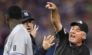 First base umpire Tom Hallion, right, ejects New York Yankees pitcher Luis Severino from the game after he charged Toronto Blue Jays' Justin Smoak after hitting him with a pitch during second inning American League baseball action, in Toronto on Monday, Sept.26, 2016. THE CANADIAN PRESS/Frank Gunn