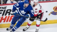 Toronto Maple Leafs' Colin Greening, left, and Ottawa Senators' Thomas Chabot battle for the puck during third period NHL preseason hockey action in Halifax on Monday, September 26, 2016. THE CANADIAN PRESS/Darren Calabrese