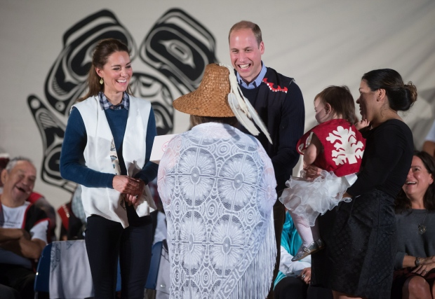 Wearing First Nations vests they were given, Britain's Prince William, the Duke of Cambridge, and Kate, the Duchess of Cambridge, are presented with a doll for Princess Charlotte during a welcoming ceremony at the Heiltsuk First Nation in the remote community of Bella Bella, B.C., on Monday September 26, 2016. THE CANADIAN PRESS/Darryl Dyck