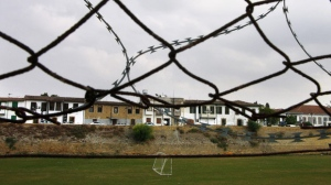In this Wednesday, Nov. 6, 2013 photo, barbed wire on a wall near the soccer pitch inside the United Nations controlled buffer zone separating ethnically-split Cyprus in the capital Nicosia. In an effort to do away with decades of isolation, the president of the breakaway Turkish Cypriot soccer association said on Monday March, 30, 2015, he's determined to follow through with a decision to join the Cyprus Football Association. (AP Photo/Petros Karadjias)