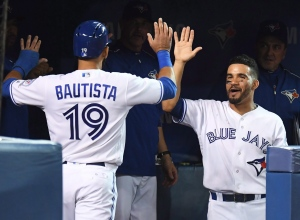 Toronto Blue Jays' Jose Bautista and Devon Travis celebrate after Bautista scored on an RBI double batted by teammate Troy Tulowitzki, not shown, during third inning American League baseball action against the New York Yankees, in Toronto on Monday, Sept.26, 2016. THE CANADIAN PRESS/Frank Gunn
