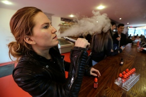 In this Feb. 20, 2014 photo, Talia Eisenberg, co-founder of the Henley Vaporium, uses her vaping device in New York. (AP Photo/Frank Franklin II, File)