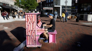 "In this Sunday, Sept. 25, 2016 photo Scott Frazer, of Medford, Mass., plays a piano on the sidewalk in the Harvard Square neighborhood of Cambridge, Mass. A number of working pianos painted by local artists have been placed around Boston and Cambridge, each with a simple message to passersby: ""Play Me, I'm Yours."" (AP Photo/Steven Senne)"