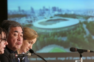In this Jan. 15, 2016 file photo, Japanese architect Kengo Kuma, second left, speaks about his design of the 2020 Tokyo Olympic stadium during a press conference in Tokyo. (AP Photo/Eugene Hoshiko)