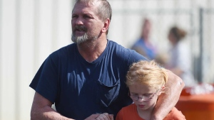 Joey Taylor walks with his daughter Josie Taylor after picking her up at Oakdale Baptist Church on Wednesday, Sept. 28, 2016, in Townville, S.C. (AP Photo/Rainier Ehrhardt)