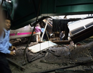 In a photo provided by William Sun, people examine the wreckage of a New Jersey Transit commuter train that crashed into the train station during the morning rush hour in Hoboken,, N.J., on Thursday, Sept. 29, 2016. (William Sun via AP)