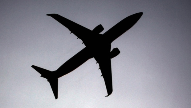 A silhouette of an airplane flying overhead. (AP)