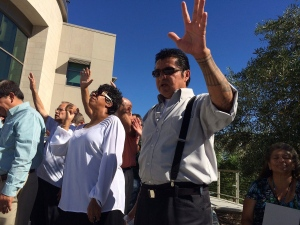 Pastor Richard Cisco Mendez, right, joins members of the community praying outside El Cajon Police Department station in El Cajon, Calif., on Friday, Sept. 30, 2016. Ministers led dozens of people in a prayer for unity, healing and peace Friday in a San Diego suburb following days of angry and sometimes violent protests over the police killing of an unarmed black man. The prayer service comes ahead of what's expected to be a large protest Saturday by the family of Alfred Olango and demonstrators upset over his killing and demanding the release of a video showing the incident. (AP Photo/Julie Watson)