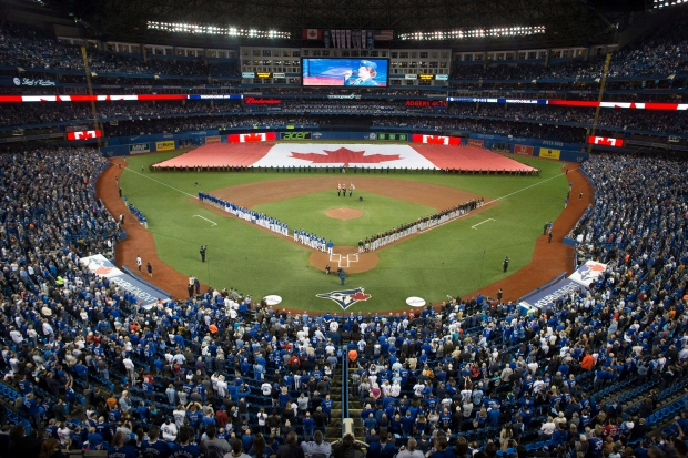 The Canadian flag is unfurled during the singing of the Canadian national anthem before the start of a American League wild-card game between the Toronto Blue Jays and the Baltimore Orioles in Toronto on Tuesday, October 4, 2016. THE CANADIAN PRESS/Chris Young