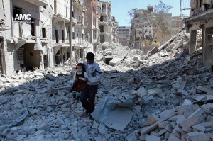 In This April 21, 2014, file photo, provided by the anti-government activist group Aleppo Media Center (AMC), which has been authenticated based on its contents and other AP reporting, shows a Syrian man holding a girl as he stands on the rubble of houses that were destroyed by Syrian government forces air strikes in Aleppo, Syria. (AP Photo/Aleppo Media Center AMC, File)