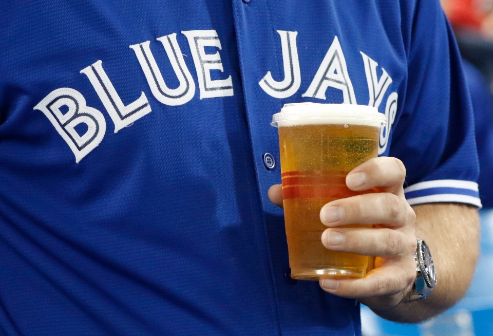 A man holds a beer in a plastic cup before the Toronto Blue Jays play the Texas Rangers play in American League Division Series action in Toronto on Sunday, October 9, 2016. THE CANADIAN PRESS/Mark Blinch