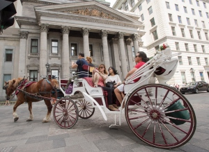 Tourists ride a caleche past the original Bank of Montreal head office on Tuesday, May 31, 2016 in Old Montreal. (The Canadian Press/Ryan Remiorz)